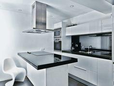 #reforma #cocina de muebles blancos con encimera color negro, isla central para zona de cocción y pequeña barra.