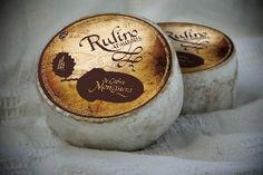 queso afinado de cabra de pasta semiblanda, con forma cilíndrica y corteza naranja, lisa y pegajosa