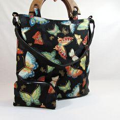 Klára motýlková kabelka,kabela,taška pro všestranné využití do práce,do školy na výlet ušitá z krásné bavlněné látka se vzorem motýlů,různě barevných spodní oválný díl a všité spodní díly i zadní díl jsou z černé koženky taška má jednoduchý tvar vyztužená ronarem zipové zapínání tašku zdobí dřevěná ucha vyrobena v malé truhlářské dílně a ...