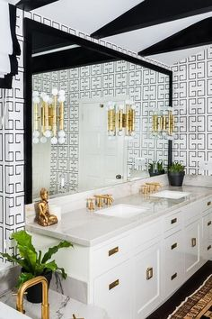 White and black bathroom features a white ceiling accented with glossy black moldings placed above walls clad in Noir Greek Key Wallpaper lined with a white double washstand with aged brass campaign hardware and brass square pulls.