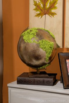 We painted this basic globe a metallic hue then glued faux-moss over the continents for a trendy, upscale piece of table decor.: