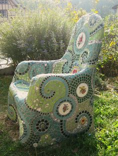 Regular metal garden chair. Cover with chicken wire and concrete (or hessian soaked in hypertufa?) then mosaics.