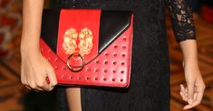 A model is holding a Bellorita red and black hand tooled and hand painted leather PX crossbody clutch on her hand.