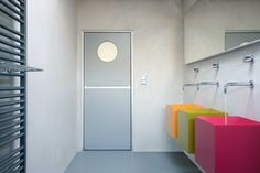 colorful wash sinks and a grey modern interior door with a porthole