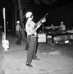 Cleveland, 1966 A police officer aims a Tommy gun toward the roof of a theater in the riot-torn Hough area in Cleveland, on July 19, 1966. The riot began with two separate incidents of discrimination at the white-owned Seventy-Niners' Café—one in which a prostitute was ordered to leave and another in which an African-American man was denied service. Soon, a crowd had gathered and police were dispatched. After the first night, one woman had been killed and three had been injured by bullets…