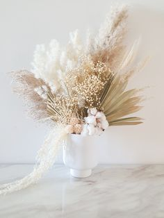 Combination of dried pampas, ming fern, palms, gyps, cotton stem, wheat, scabiosa and hanging amaranthus with a neutral palette.