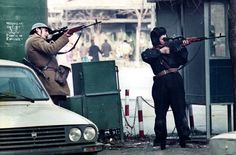 Romanian soldiers, their communist insignia removed, take aim with their PSL rifles during the 1989 Romanian Revolution.