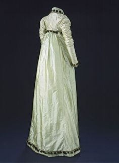 Green chenille pom-poms decorate this silk taffeta spencer and matching dress. They are attached to a continuous silk cord and stitched into place around the collar, cuffs and down the front of the bodice.