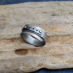 The lightness and dark grey color of titanium still amazes me. I made this band yesterday.  With sterling silver and 14k gold rivets. Fun to make.  #titaniumjewelry #titaniumring #ringband  #riveted #knewconcepts #rusticjewelry #metalworking #metalwork #c