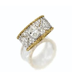 DIAMOND BAND RING, BUCCELLATI Set with an oval-shaped diamond weighing approximately .60 carat, within an openwork frame accented with small round diamonds, mounted in 18 karat white and yellow gold, size 6, signed M. Buccellati, Italy. With signed box.