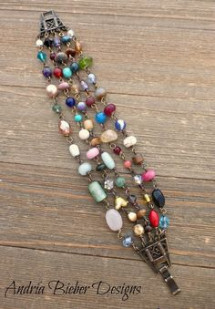 Mixed colors. Wire wrapped multi strand Czech glass and stone, with bronze metal bracelet.