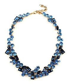 Accent your neckline with this statement piece that features a collection of shapes in a deep ocean hue.