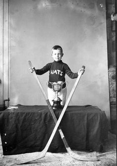 A young lad posing in a Nationals Hockey Team jersey/sweater with a pair of sticks and trophy, 1920.