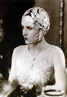 Cloche Cap, (1920's) Comprised of silver leaves curling flatteringly around the cheekbone and jawline in a flower bloom shape with one leaf deliberately low, just touching the eyebrow line, interlocking leaves continue around the cap.