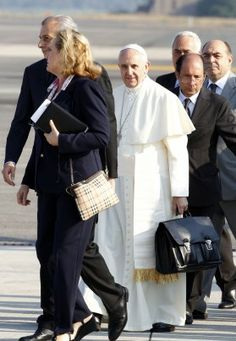 Francis caused a stir by carrying his own black hand luggage to his flight to Brazil on July 22. He even kept holding it while shaking hands with VIP well-wishers and while climbing the stairs to the jet\'s entrance.
