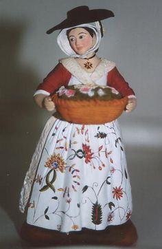 """Arlésienne 1770 La chanoinesse= coiffe surmontée d'une """"velette"""" triangulaire, dont les 2 barbes se croisent sous le menton et se nouent sur la tête peut, ou non, être surmontée d'un chapeau noir en feutre en hiver, en paille en été- la jupe est faite en boutis- le tablier brodé au point de Beauvais- le """"droulet"""", ce gilet à 2 ou 3 longs pans à l'arrière-autour de son cou, la croix de Malte."""