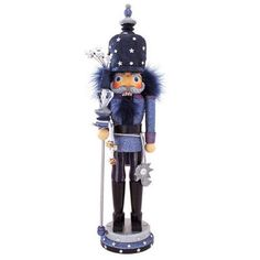 "Shimmering with a dazzling array of eye-catching glitter and reflective acrylic gemstones, this spectacular figure is certain to be the <i>star</i> of your nutcracker collection! Artfully crafted of wood and resin with midnight blue feather accents, our Night Stars Nutcracker measures 19"" tall and is depicted holding a ceremonial baton adorned with ribbons of silver jingle bells. Featuring a lever on his back that moves his jaw up and down in true nutcracker fashion, this stellar collectible…"