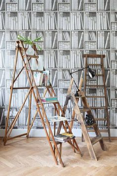 In the living room, Cole & Son Ex Libris wall paper provides a focal feature  backdrop for vintage ladders, which offer imaginative shelves for displaying vintage finds and favourite pieces.