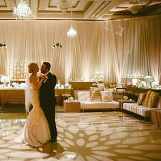 Brides.com: . Gobo lighting creates a vision of elegant flowers across the dance floor in this chic, sophisticated ballroom decorated in an ivory, champagne, and gold palette.