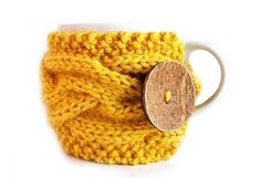 COFFEE COZY -  Know a coffee fiend or two? Keep their hands cool with a crocheted cozy that trumps disposable paper sleeves any day. The wooden or coconut button comes at no extra cost, each of them hand carved with a unique color, pattern and texture.   from Etsy