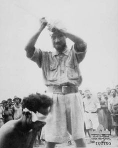 A photograph found on the body of a dead Japanese soldier showing Private (Pte) Reharin, member of the Netherlands East Indies (NEI) Forces wearing a blindfold about to be beheaded with a sword by Yunome Kunio. A group of local people and Japanese stand watching in the background and the soldier to Yunome's left is 3rd Class Warrant Officer Fukuda. The execution was ordered by Vice Admiral Kamada, the commander of the Japanese Naval Forces at Aitape. New Guinea: Aitape. 24 October 1943.