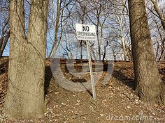 A No Trespassing sign on an embankment, posted by Norfolk Southern Corporation, protects a now abandoned railway. The defunct railroad could be a real danger to kids, teenagers, or curious adults who might be tempted to wander up to the isolated, decaying tracks. Exemplifying the potential danger, old railroad ties rest behind the sign, on the ground near the tracks.