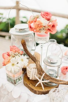 Wedding dinner reception centrepiece, with coral-coloured roses, starfish, driftwood, nautical knot and lanterns with candles on the wood plate base.