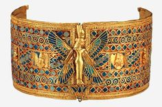 Queen Amanishaketo's armlet: Gold with fused-glass inlays.Worn on upper arm or wrist.Closed by fastening either leather or linen. Over the hinge is separately worked figure of a four winged goddess standing on a papyrus umbel. On top of her vulture diadem she wears the Double Crown & thus identified as the goddess Mut, consort Anum.