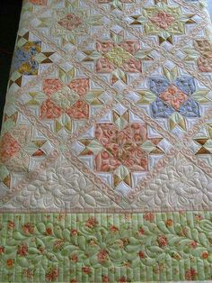 Quilt pieced by Nancy Philabaum. Quilted by Jessica Jones. Border and triangle motifs by Linda Lawson. No pattern info was provided. https://www.flickr.com/photos/jessicasquiltingstudio/5738195082/in/photostream