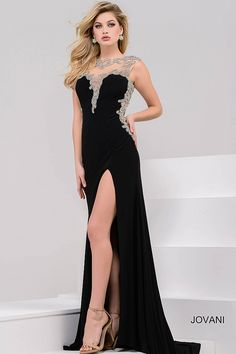 Sexy floor length form fitting black jersey evening gown with high slit features sleeveless bodice with sheer crystal embellished neckline and sides and an open back.