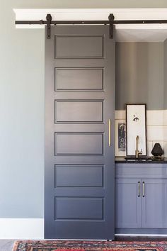 Alyssa Rosenheck Sara Ray Interior Design - A gray wet bar, finished with a gray paneled sliding door on rails, is filled with gray bar cabinets topped with black quartz fitted with a curved sink and brass gooseneck faucet.