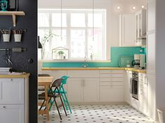 Et hvidt køkken med hvide LAXARBY låger, en KARLBY bordplade af birk og grønne detaljer