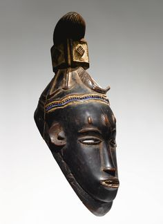 Africa | Guro Female Mask, Gu, Ivory Coast. c. 1970. | In Guro religious practice, masks representing idealized ancestors are employed in the masquerades of family cults and secret societies.  The mask above represents gu, the wife/daughter of zamble.
