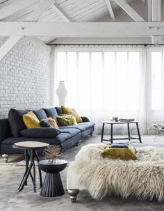 Relaxed boho vibes in this loft with Ikea sofas with Designer Guild, linen covers, sheepskins and the famous Harry Bertoia Bird chair in this inspiring french loft!