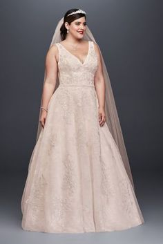 Crafted of tulle over lace for added dimension, this Oleg Cassini A-line plus-size wedding gown has been appliqued with metallic-embroidered and sequined blossoms. The tank bodice opulently outlined with over 3,000 beads at the V-neckline, arms, and waist. The look is finished with a low back and sheer side insets on the bodice. Oleg Cassini, exclusively at David's Bridal Plus size Polyester Chapel train Side pockets Back zipper; fully lined Dry clean Imported Also available in