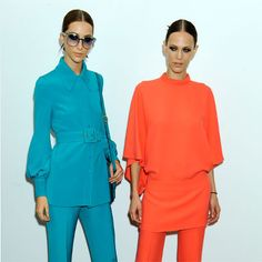 Models wearing turquoise and coral neon Tunic and Trousers by Gucci
