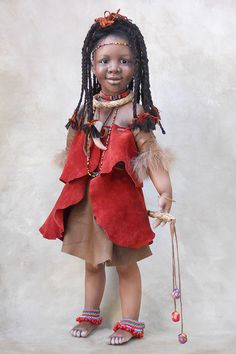 Umba is a gentle African child with a soft smile. She is all ready to preform her tribal dance. Her ethnic costume is made of rust and brown suede with leather, feathers, raffia and beads. Her long hair is braided with yarn and leather to complete her unique traditional attire.
