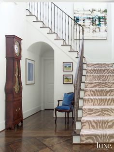 In the entry, Goforth placed a grandfather clock—a wedding gift from the wife's parents—an antique French cane chair upholstered with Kravet fabric and a pair of landscape paintings from Meredith Long & Company. A zebra-print stair runner from Stark strik Staircase Landing, White Staircase, Staircase Runner, Staircase Remodel, Staircase Design, Stair Runners, Foyer Staircase, Staircase Makeover, House Stairs