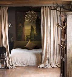 bedroom inspiration photo.  Like the old idea of closing in the immediate bed area by fabric.  But it seems impractical, especially with my love of fans.