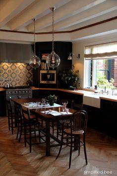 eat in kitchen with black cabinets + herringbone floor + geometric backsplash + globe pendants