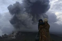 A mother holds her son as they watch the eruption of Mount Sinabung at Berastepu village in Karo district, Indonesia's North Sumatra provinc...