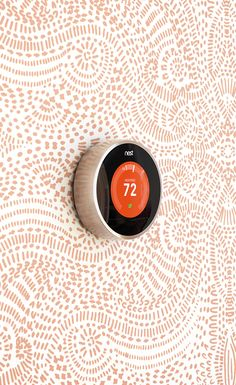The metallic ring on the Nest Thermostat reflects and blends with its surroundings.