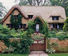 Cottage-Style Home Ideas Plucked from the pages of a storybook, this quaint cottage-style home uses architecture and landscape to create a casually beautiful curb appeal. A wide wooden gate and tall stone fence both feel aged and perfectly in place, as do Storybook Homes, Storybook Cottage, Fairytale Cottage, Garden Cottage, Tudor Cottage, French Cottage, English Cottage Exterior, Brick Cottage, Cottage Windows
