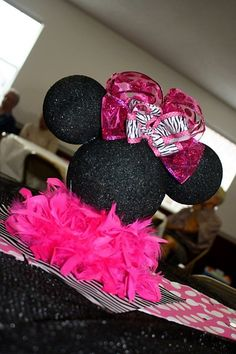 Minnie Mouse birthday. Possible centerpiece for the food table. Black styrofoam balls, stick 'em together with wooden skewers, attach ribbon & a boa. Boom. I can handle that.