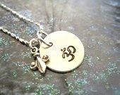 """This Pretty sterling silver 1/2"""" disc stamp with the """"Om"""" symbol which is thought to be the most desirable mantra to use while meditating and a tiny Fleur De Lis sterling silver charm hanging delicately next to it. Comes on a sterling silver chain in a pretty organza bag.    MEMBER - TheSilverBuddha"""