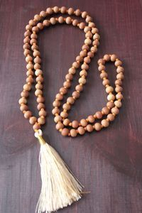The sandalwood mala has a calming and peaceful scent that gently raises one's vibration. It is known to encourage clarity, tranquility, and positive energy. Wearing this mala can boost the immune system and promote healing. It has a cooling effect, assists with depression and clairvoyance.