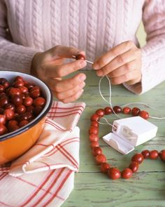 The best material for stringing cranberry or popcorn garlands is inside your medicine cabinet. Waxed floss is strong and slick, so cranberries and popcorn will slide on easily. Knot one end of a piece of floss and thread a needle onto the other; just pierce through items and slip them on.