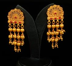 Gold Earring With antique spinnel garu polish earrings. Reminiscent of glistening dewdrops in golden sunshine, dusted with crystallized raspberry syrup, these gold earrings are crowned by a symphony of semi-circular filigree work in gheru polish, to impart an antique finish. The blood red Spinel provides the ideal contrast against the warm glow of gold. The earrings are enhanced with four rows of cascading gold balls which are interspersed with bunches of tiny gold beads.