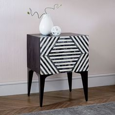 With its hand-inlaid pattern of black and white tiles, the Bone Nightstand isn't afraid to make a bold statement. It's perched on slim legs so you can fit baskets or books neatly underneath.