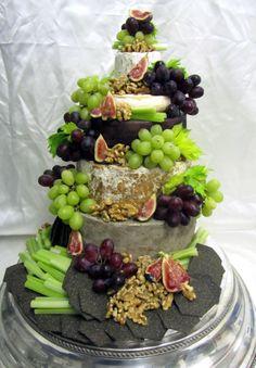 Juusto pyramidi: juuston ystäville erillaisia kokonaisia juustoja hedelmi, pähkinöitä ja keksejä - Cheese pyramide for the cheese lover, selection of cheeses fruits nuts and crackers